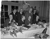 Several hoteliers and others gathered at a long table around a ledger, Los Angeles, 1930s