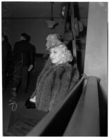 "Mae West sitting in court during questioning about earnings from her role in the movie ""She Done Him Wrong,"" Los Angeles, 1940"