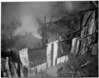 Firefighters walk through the ruins of a fire that occurred at Dura Steel Products Co., Los Angeles, 1940