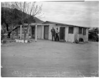 Two unidentified men stand outside the deserted Palm Springs cabin where Betty Hardaker hid after murdering her daughter Geraldine Hardaker, Los Angeles, 1940