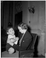 Miss Leo C. Moore sitting on a bench holding her young child, Los Angeles