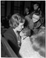 Miss Leo C. Moore sitting in a crowd holding her young child, Los Angeles