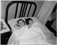 Young girls Barbara and Rosalie Bell laying next to each other in a twin-sized bed, Los Angeles