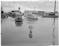 Automobiles drive through flooding at McKinley Ave. and Manchester Ave., Los Angeles, February 25, 1940
