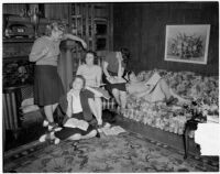 Group of young women read books and write together at their USC sorority house, Los Angeles, 1940
