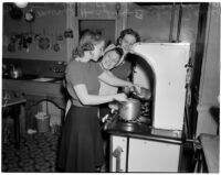 Three USC sorority sisters cook by a stove, Los Angeles, 1940