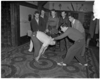 USC Kappa Alpha members spank another member with a wooden paddle inside their fraternity house, Los Angeles, 1940