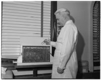 Dr. Raymond L. Carey with honeybees used to treat his patients' arthritis, Los Angeles, November 9, 1941