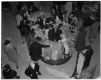 Crowd of shoppers gathered around a table of rayon print dresses during the semiannual Dollar Day sale in downtown Los Angeles, February 17, 1940
