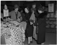 Women looking through a pile of rayon print dresses during the semiannual Dollar Day sale in downtown Los Angeles, February 17, 1940