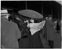Two women under an umbrella on a rainy Derby Day at Santa Anita Park, Arcadia, February 22, 1940