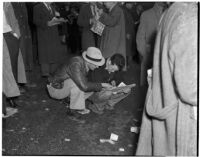 Two men reading the race listings on a rainy Derby Day at Santa Anita Park, Arcadia, February 22, 1940