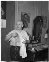 Euclide Allard, 66, holding a piece of twine and a towel used by a burglar to tie up Allard in his hotel room, Los Angeles, February 16, 1940