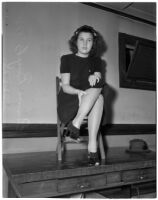 Emma Boyts, 15, sitting on a chair on top of a desk, Los Angeles, November 13, 1939