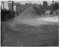 Burst fire hydrant flooding 1st and Main St. in downtown Los Angeles, circa 1940