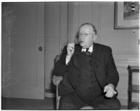 Oklahoma Governor Leon C. Phillips sitting in a chair and lighting a cigar, circa 1940