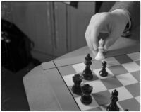 Close-up of a chess board and player's hand moving one of the white bishops, Los Angeles
