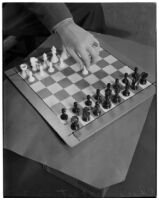 Top view of a chess board and a player's hand making the first move of the game, Los Angeles