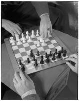 Top view of a chess board and both of the players' hands, one of the players is moving the white knight, Los Angeles