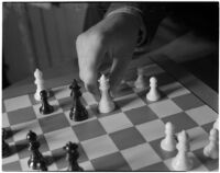 Close-up of a chess board and a player's hand moving the white queen, Los Angeles