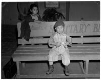 Young boy sits on a bench in Chinatown, Los Angeles, 1930s