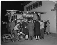 Crowd gathers around Charlie Chan, fortune teller, in Chinatown, Los Angeles, 1930s