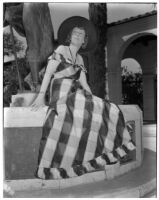 Mrs. Priestly A. Horton sitting on the base of a statue, Los Angeles, circa 1940