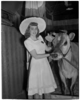 """Donna Larson and Elsie the Borden Cow, star of the 1940 film """"Little Men,"""" Los Angeles, 1940"""