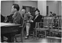 Attorney at table and spectators and witnesses seated behind him during unidentified hearing in courtroom with model cars on table