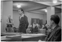 Man testifying (?) during unidentified hearing in courtroom with model cars on table