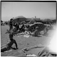 Group sits under umbrellas on a crowded beach on Labor Day, Los Angeles, September 3, 1945