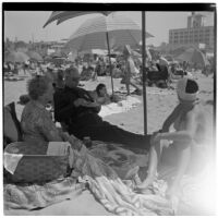 Two women and a man have a picnic under umbrellas at the beach on Labor Day, Los Angeles, September 3, 1945