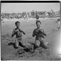 Two boys cover themselves with wet sand at the beach on Labor Day, Los Angeles, September 3, 1945