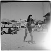 Woman serving a volleyball at the beach on Labor Day, Los Angeles, September 3, 1945