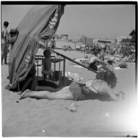 Two woman and a baby in a crib under an umbrella at the beach on Labor Day, Los Angeles, September 3, 1945