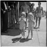 Two young girls in matching overalls eat snow cones on Labor Day, Los Angeles, September 3, 1945