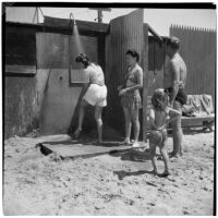 Two women, a man, and a young girl in line for the outdoor shower at the beach on Labor Day, Los Angeles, September 3, 1945