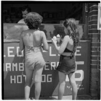 Two young girls buying snow cones on the boardwalk on Labor Day, Los Angeles, September 3, 1945