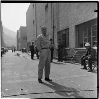 Walter Bush stands outside of a guarded building, Los Angeles, 1930s