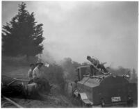 Fire fighting crew uses a small bulldozer to clear brush after a fire in La Canada, Los Angeles, October 1945