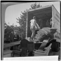 Louis M. Rich family watches as their possessions are loaded into a moving van, Los Angeles, November 22, 1945