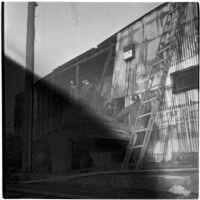 Fire fighters battling a fire in a hay barn, Los Angeles, 1945