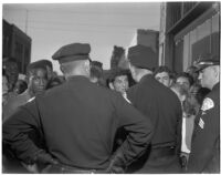 Three policemen face a crowd on young people on a city street, Los Angeles
