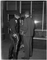Policeman and man wearing a suit and hat facing a young man in a plaid shirt, Los Angeles