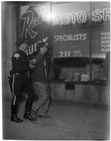 Man in custody of a policeman in front of Red's Auto Shop, Los Angeles