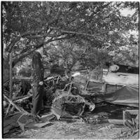 Policeman Charles L. Nelson inspects the wreckage of a plane crash, Los Angeles, 1945