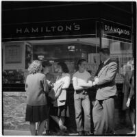 Woman and man talking to truant teenagers standing outside a jewelry store, Los Angeles, March 1946