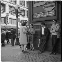 Woman talking to truant teenagers standing against a building, Los Angeles, March 1946