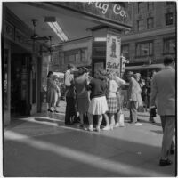 Woman talking to truant teenagers standing outside a drugstore, Los Angeles, March 1946