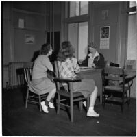 Mrs. Mallie Kerr sits at her desk across from two teenage girls, Los Angeles, 1946